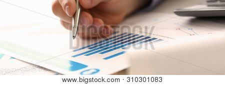 Businessman Controlling Prices Accounting Income. Man Hold Pen, Check Financial Data On Paper Chart,