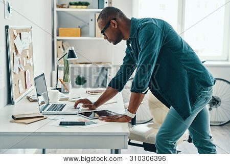 Business Expert. Handsome Young African Man In Shirt Using Laptop While Standing In The Office