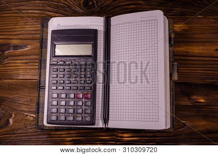 Opened Notepad, Scientific Calculator And Pencil On Rustic Wooden Table. Top View
