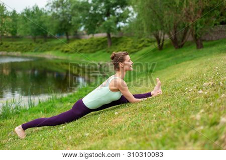 Slim Young Brunette Girl Yogi Does Difficult Yoga Exercises On The Green Grass On The Background Of