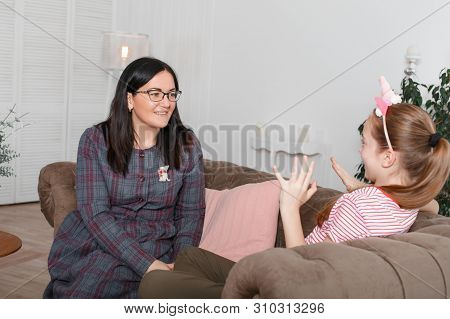 Mom And Daughter Are Sitting On The Couch And Chatting. Girl Teenager With Emotions Tells Her Mother