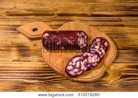 Cutting Board With Sliced Salami Sausage On Rustic Wooden Table