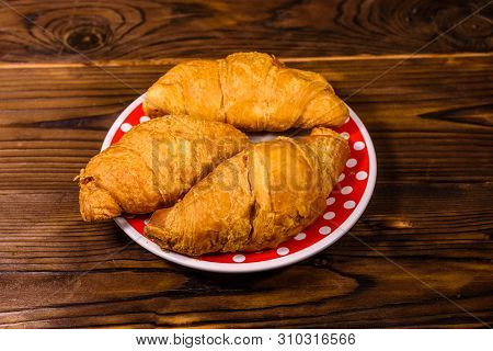 Plate With Croissants On Rustic Wooden Table