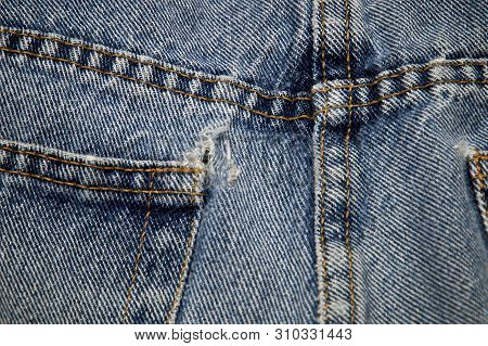 Close Up View Of Double Sewn Seams And Frayed Hole On Pocket Of Old Blue Jeans.