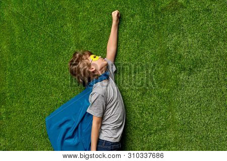 From above side view of little boy in superhero cape and mask pretending to fly up in heroic pose while lying on green lawn poster