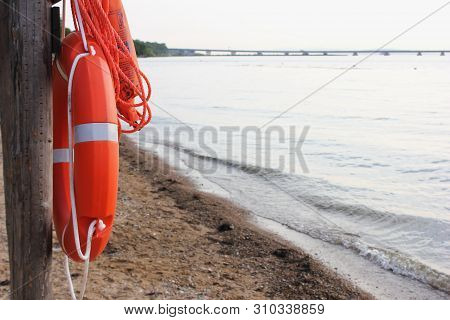 Orange Lifeline Hanging On A Wooden Structure Near The Sea On The Beach. The Concept Of Water Safety