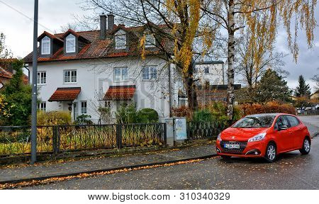 Residential House With A Tile Roof. Red Car On A Road. Rural Landscape. Fall. Yellow Leaves. Picture