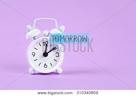 Procrastination, delay and urgency concept. White alarm clock with a sticky note with text tomorrow poster