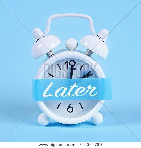 Procrastination, delay and urgency concept. White alarm clock with a sticky note with text later. poster