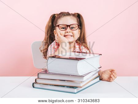 Smiling Blond Little Cute Girl Studying On Books.