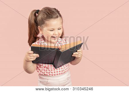 Little Cute Girl Reading Book And Smiling On Pink Background.