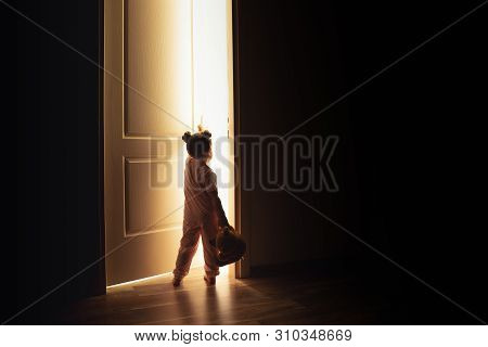 Little Girl Opens The Door To The Light In Darkness.