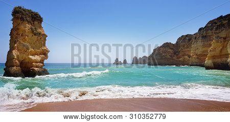 Beautiful Landscape: Cliffs In Turquoise Atlantic Ocean Near Beach Praia Dona Ana, Lagos, Portugal