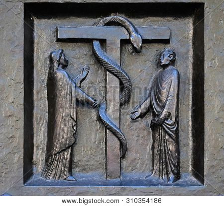 ZURICH, SWITZERLAND - JUNE 23, 2018: The redemptive death of Christ depicted in the emblem of the bronze serpent, relief on the door of the Grossmunster (