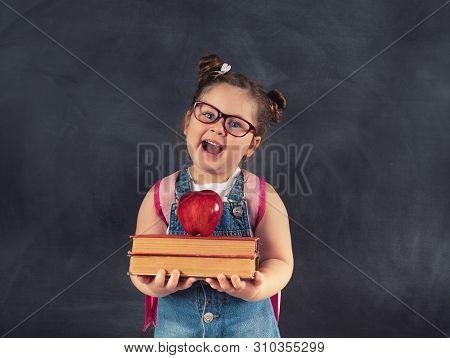 Little Cute Child Holding Books On Blackboard.education Concept