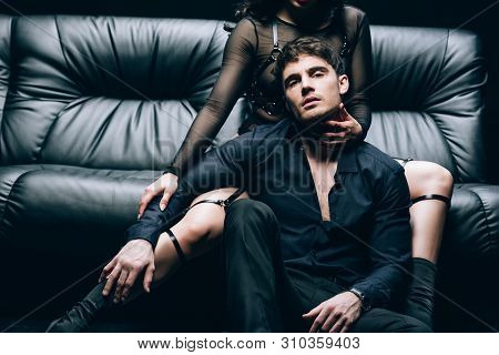 Passionate Handsome Man Sitting Near Sexy Woman In Bdsm Costume On Black Leather Sofa