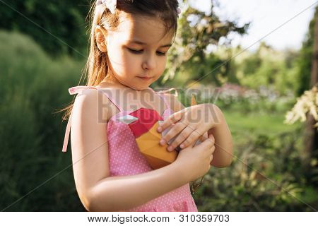 Closeup Portrait Of Cute Little Girl Holding Colorful Paper Bird In The Park. Adorable Child Playing