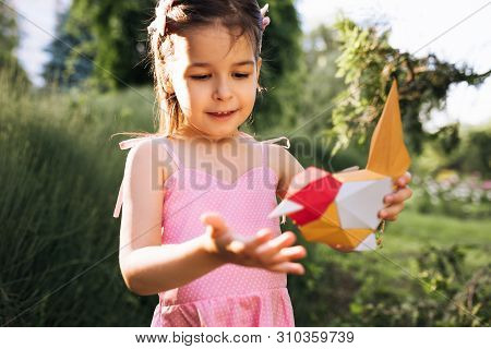 Happy Cute Little Girl Holding Paper Colorful Bird In The Park. Child Playing With A Bird Toy Outdoo