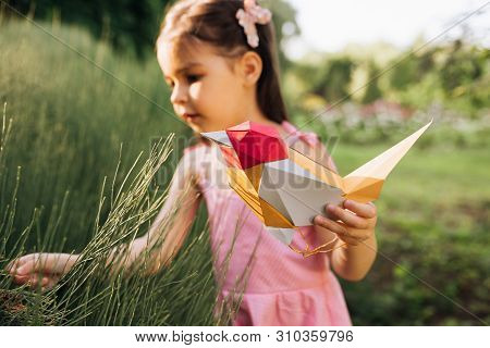 Curious Cute Little Girl Holding Paper Colorful Bird And Exploring Plants In The Park. Ecology, Envi