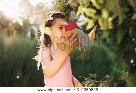 Side View Image Of Cute Little Girl Holding Paper Colorful Bird In The Park. Happy Child Playing A B