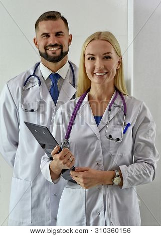 Smiling doctors greet patients. Male practitioner in white robe. Physicians. Female doc with a stethoscope. Greeting. Hello. Healthcare. Treatment. Medicine. Happy medics. Clinic specialists. poster