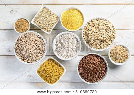 Selection Of Whole Grains In White Bowls - Rice, Oats, Buckwheat, Bulgur, Porridge, Barley, Quinoa,