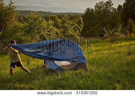 Guy Lay A Tent On The Grass. Forest And Mountains In The Background. The Sun Comes In And The Sky Is