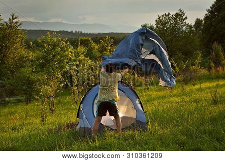Guy Lay A Tent On The Grass.forest And Mountains In The Background. The Sun Comes In And The Sky Is