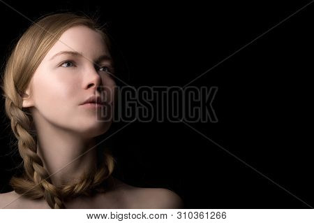 Portrait Of A Beautiful Girl Of Slavic Appearance With A Braid Haircut On A Black Background.