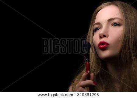 Portrait Of A Beautiful Blonde Who Uses A Makeup Brush On A Black Background.