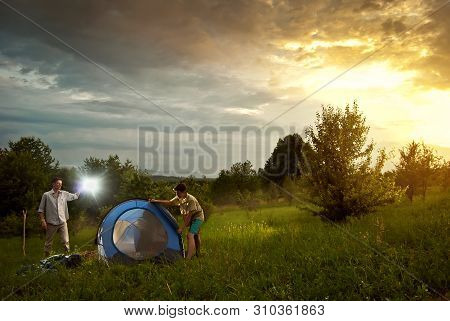 Guys Lay A Tent On The Grass. A Man Teaches The Boy To Camp Out. Forest And Mountains In The Backgro