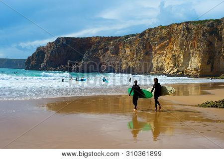 Surfers With Surfboards On The Beach. . Algarve, Portugal