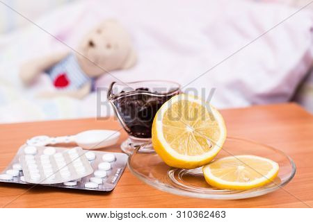 Medicines, Vitamins, Lemon And Jam On The Table Against The Background Of A Children's Bed With A So