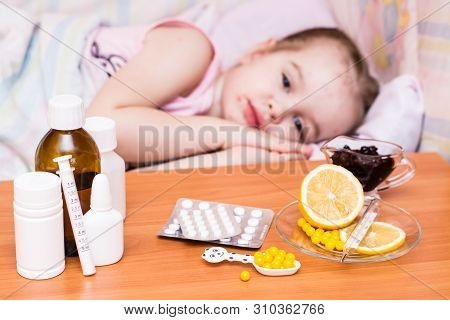 Medicines And Vitamins On The Table Against The Background Of A Child In A Bed That Has Chickenpox