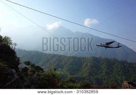 Lukla, Nepal - May 8, 2019: Small propeller airplane approaching Tenzing–Hillary Airport on background of green Himalaya Mountains in morning light