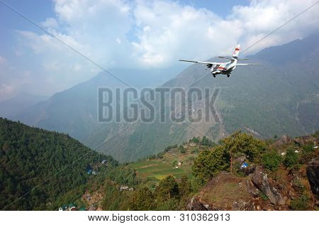Lukla, Nepal - May 8, 2019: Small propeller airplane flying from Tenzing–Hillary Airport on background of green Himalaya Mountains