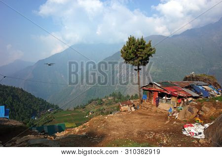 Lukla, Nepal - May 8, 2019: House made of rubbish in outskirt of Lukla and small propeller airplane approaching Tenzing–Hillary Airport on background of green Himalaya Mountains