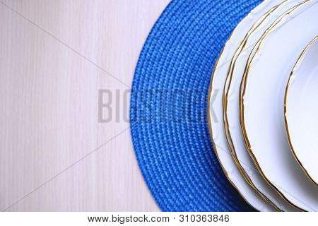 Top View Of White Plates With Gold Rim On Blue Woven Mat And On Wooden Beige Background. Selective F