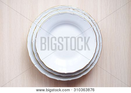 Top View Of White Plates With Gold Rim On Wooden Beige Background, Selective Focus
