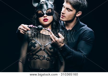 Young Man Holding Gag Near Sexy Woman In Mask And Bdsm Costume Isolated On Black