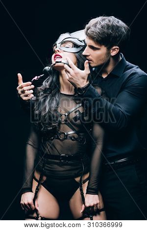 Handsome Young Man Holding Gag Near Sexy Passionate Woman In Mask And Bdsm Costume Isolated On Black