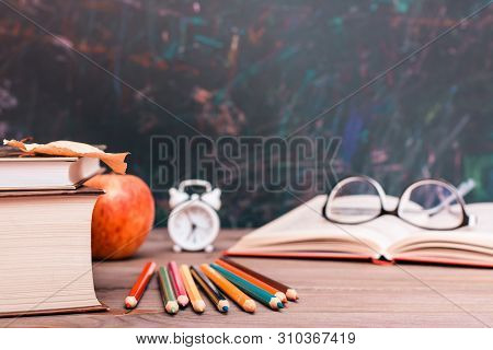 Back To School Background With Books, Pencils, Clock,  Open Book And Glasses On A Wooden Table Over