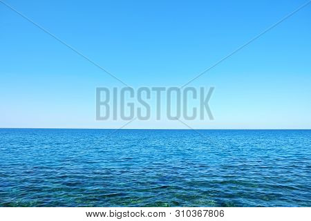 Beautiful Seascape On Sunny Day With Wind Patterns On Calm Azure Water And Clear Blue Sky Without Cl