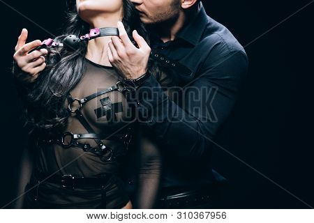 Cropped View Of Handsome Young Man Holding Gag Near Sexy Woman In Bdsm Costume Isolated On Black