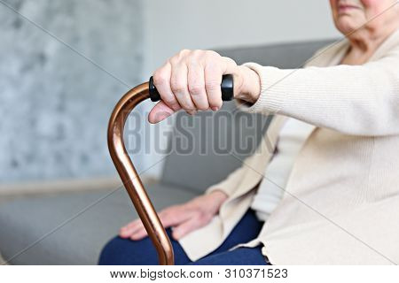 Elderly Woman Sitting In Nursing Home Room Holding Walking Quad Cane With Wrinked Hand. Old Age Seni