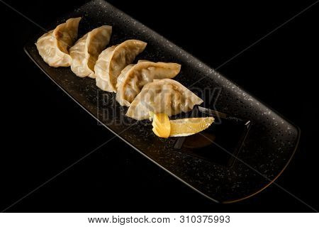 Boiled Asian Jiaozi Dumplings With Soy Sauce And Orange Slice