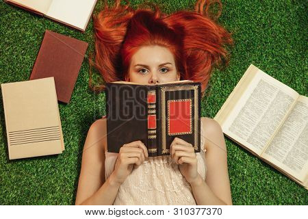 Red-haired Girl Lying On Grass And Looks From Behind The Book
