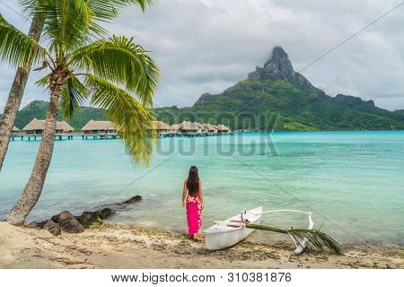 Outrigger Canoe - polynesian woman wearing sarong on Bora Bora beach by traditional vaa boat for paddling in French Polynesia. Bora Bora with Mount Otemanu and overwater bungalow resort hotel. poster