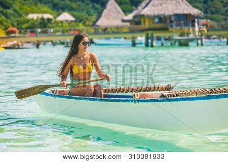 Outrigger Canoe polynesian watersport sport woman paddling in traditional vaa boat. Water leisure activity in Tahiti for recreation competition. Bora Bora overwater bungalow resort hotel.