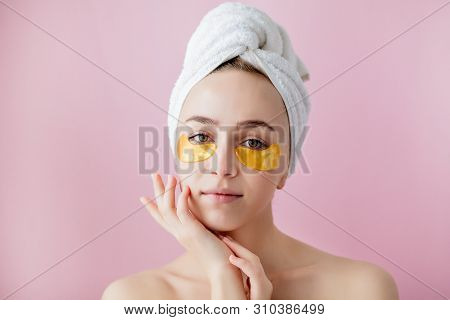 poster of Portrait of Beauty Woman with Eye Patches on pink background. Woman Beauty Face with Mask under Eyes. Beautiful Female with natural Makeup and Gold Cosmetics Collagen Patches on Fresh Facial Skin